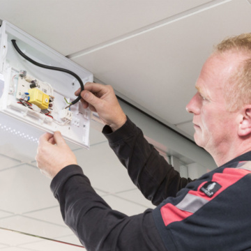 Onderhoud op een noodverlichtingsarmatuur door onze monteur