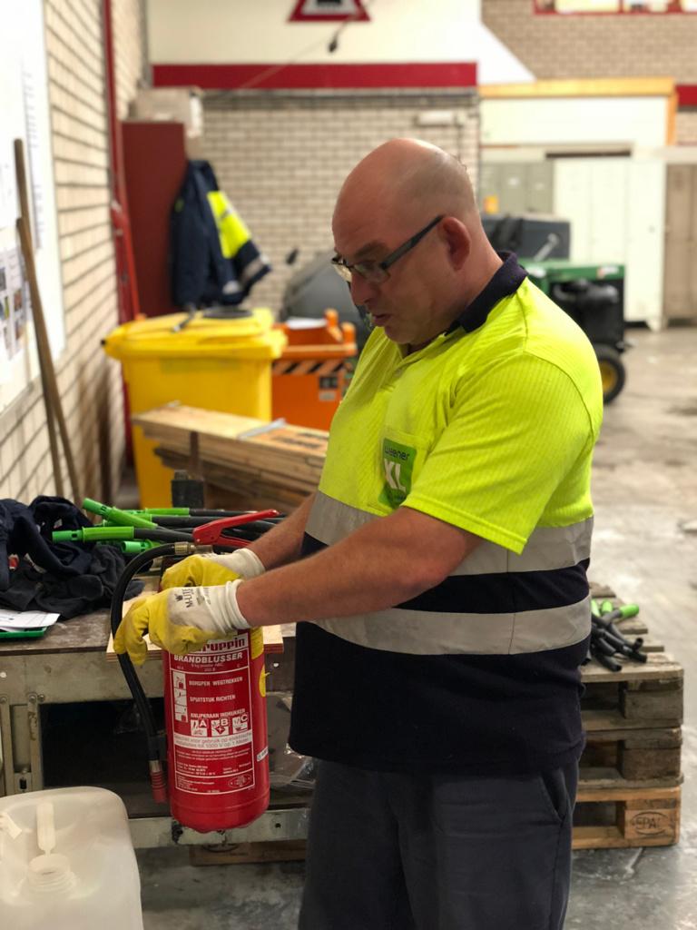 Medewerker WeenerXL bezig met ontmantelen van brandblusser